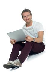 attraktiver mann mit notebook auf dem boden