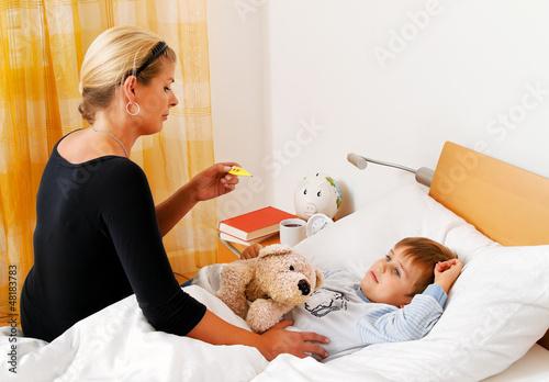 Mutter und krankes Kind im Bett. Grippe.