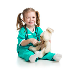 Adorable girl with clothes of doctor spoon playing with toy over