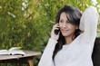 Junge Frau telefoniert auf der Terrasse