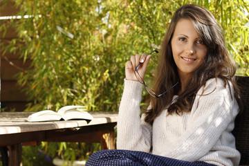 Hübsche junge Frau sitzt entspannt auf der Terrasse