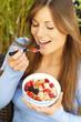 Glückliche Frau ißt Früchtemüsli
