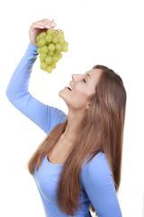 Hübsche Frau hält grüne Trauben hoch