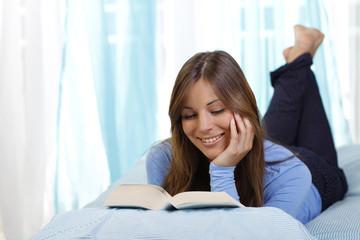 Junge Frau liest im Bett ein Buch