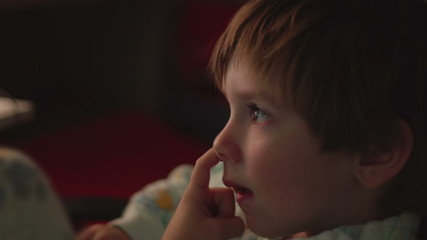 Young boy picking his nose and watching TV