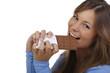 Lächelnde junge Frau beißt in eine Tafel Schokolade
