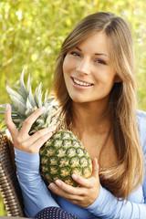 Glückliche Frau mit einer Ananas auf der Terrasse