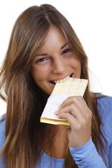 Lächelnde junge Frau beißt in weiße Schokolade