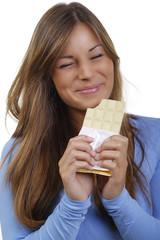 Glückliche junge Frau genießt eine Tafelweiße Schokolade