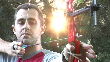 Young man shooting with bow and arrows