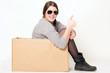 gute gelaunte Frau sitzt in einem Karton