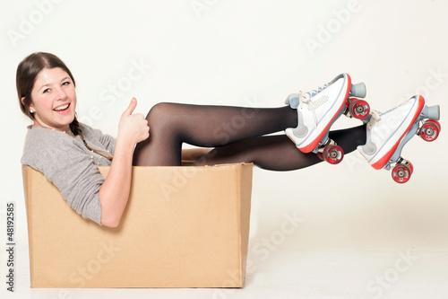 Studentin sitzt mit Rollschuhen in einem Karton