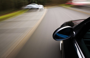 Side view of black car driving fast