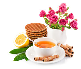 tea in cup with biscuits and lemon isolated on white background