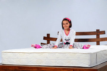 young girl sitting on the bed
