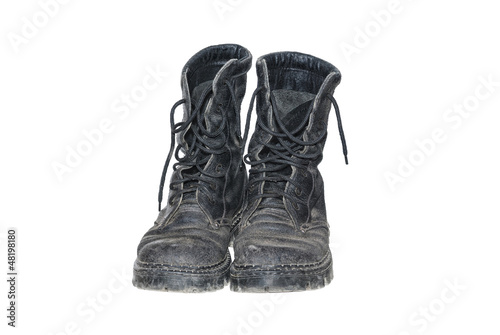 Old dirty black boots isolated on a white background