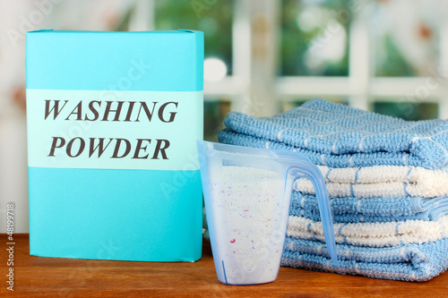 Box of washing powder with blue measuring cup and towels,