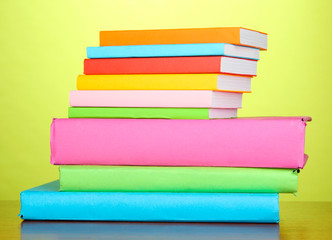 Stack of multicolor books   on green background