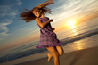 Girl jumping and dancing on beautiful beach.