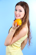 Beautiful woman with orange on blue background