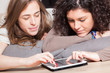 Two Beautiful Women with Tablet PC in the Bedroom