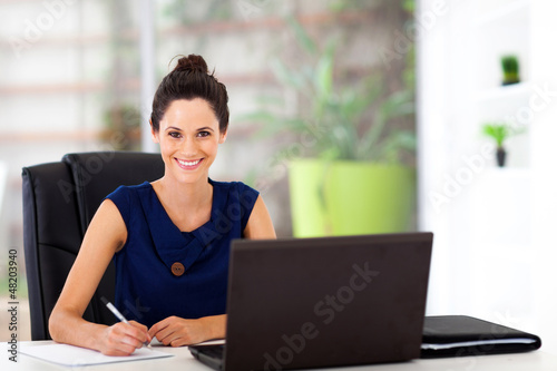 beautiful young office worker sitting by office desk