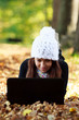 Beautiful young girl with laptop in autumn park. Young European