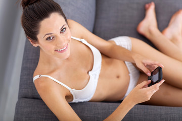 sexy young woman sitting on sofa and emailing from phone