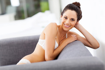 attractive young woman in lingerie relaxing on sofa