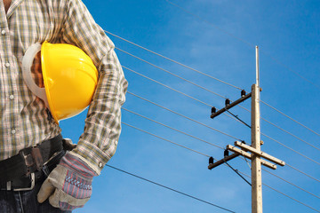 Electrician worker at work against electric post and blue sky ba