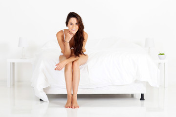 cute young woman sitting on bed