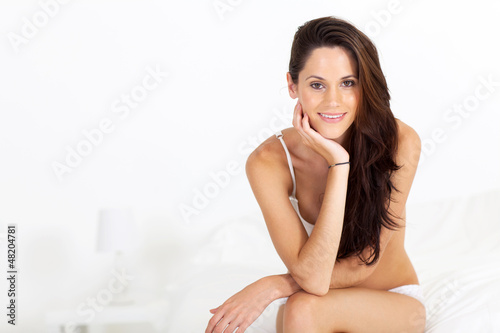 attractive young woman in underwear sitting on bed