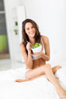 slim young woman eating green salad on bed