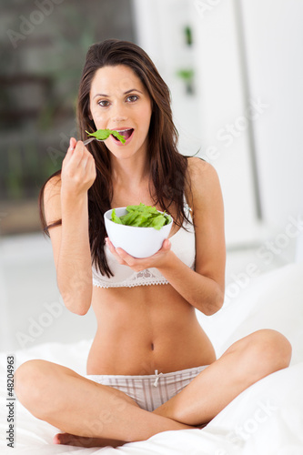 healthy young woman eating green salad on bed
