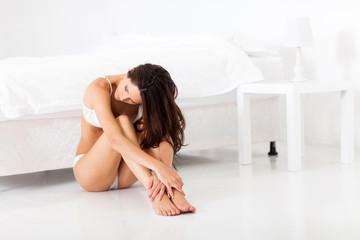 sad young woman in underwear sitting on bedroom floor