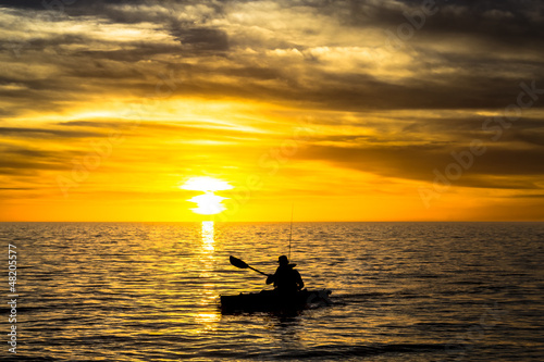 Fisherman in the kayak on the ocean in front of dramatic sunset
