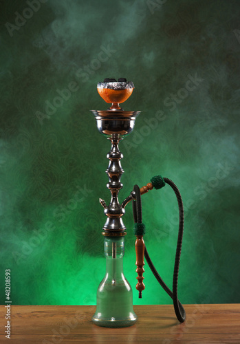 An exotic ceramic hookah on a misty green background