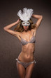 A young and sexy blond woman posing in a white mask