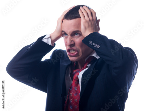 Angry young businessman holding his head
