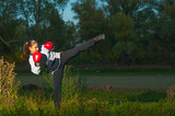 Beautiful kick boxing girl exercising kick in the nature