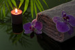 Orchid and towel with candle in night spa concept