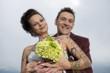 Braut mit Tatoos zeigt Brautstrauß, dahinter ihr Bräutigam