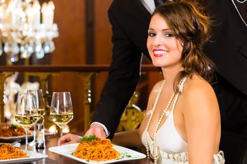 Hübsche Frau und Kellner in einem guten Restaurant