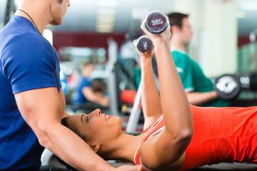 Trainer und Frau im Fitnessstudio, mit Hanteln