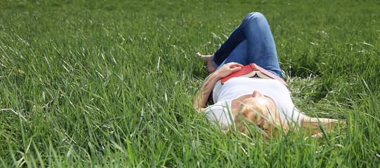 Attraktive junge Frau genießt die Sonne auf einer Wiese