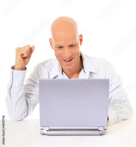 Attraktiver Mann freut sich während ihr am Laptop sitzt