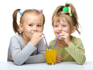 Two Little girls are drinking orange juice