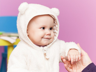 little baby in white bear costume smiles and hold mothers hand