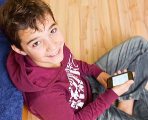 Freundlicher Junge / Kind mit Smartphone / Handy