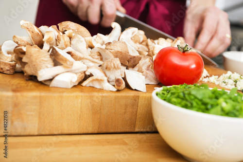 Midsection Of Man Cutting Mushrooms